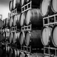 Black and white photo of stacked wine barrels.