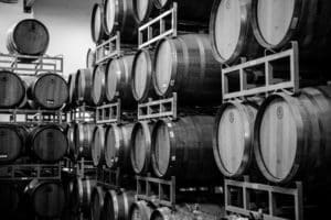 Black and white photo of wine casks stack up along a wall.