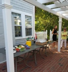 brick patio withgray table loaded with food items against a gray building with white windows and white fence