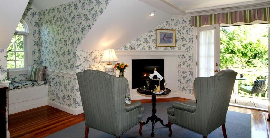 King Suite with reading nook, balcony, gas lit fireplace, green high back chairs and lavendar and green flowers on white wallpaper