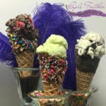 Three waffle cones filled with gelato and topped with sprinkles.