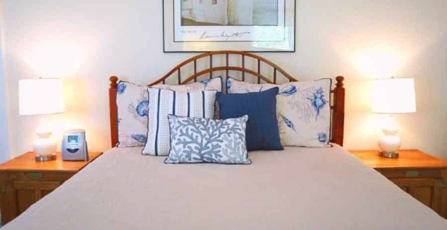 Queen Bed with Blue and cream nautical Pattern bed set two white lamps and lighthouse image on top of the bed frame