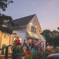 Photo of the white cottage Ice Cream Cafe at dusk.