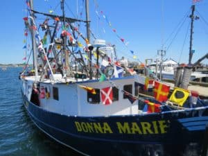 A photo of the Donna Marie boat with international flags flying on it.