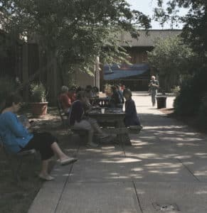 Students at the Institute on break, sitting at tables in the tree-lined courtyard.