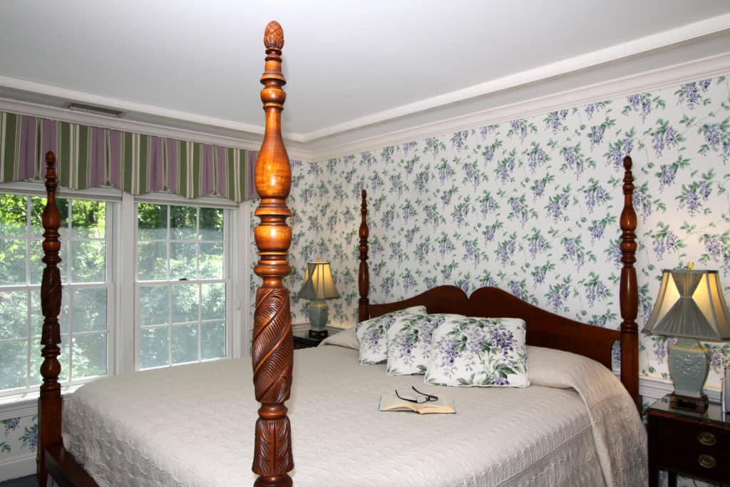 Bedroom with four-poster bed and nice window beside it.