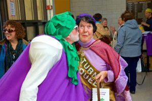 A woman in a turnip costume planting a kiss on the cheek of an older female visitor.