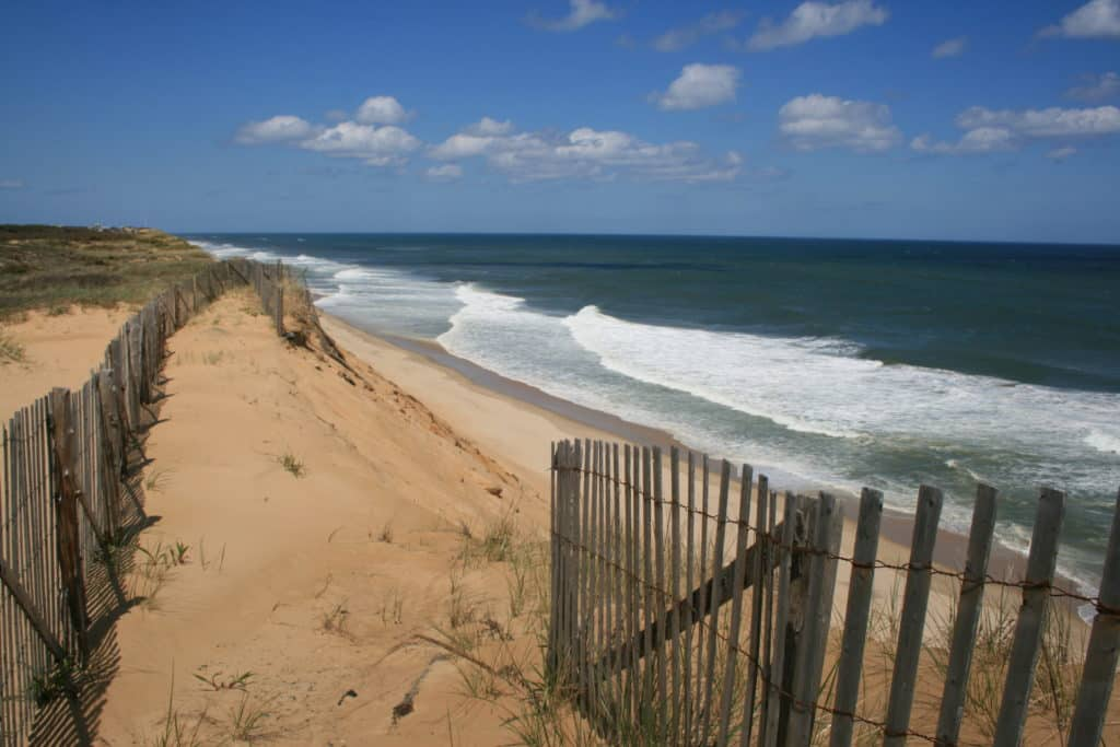 Sand dunes and sand fence against open ocean waves