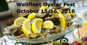 A platter of shucked oysters topped with lemon wedges.