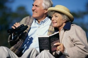 Man holding binoculars and woman holding bird book and wearing straw hat.