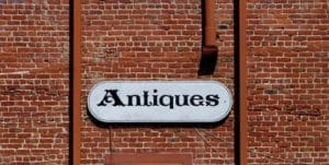 """brick wall with """"Antiques"""" sign on white board"""