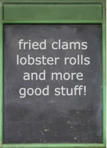 Green framed blackboard with words: fried clams, lobster rolls, and more good stuff!