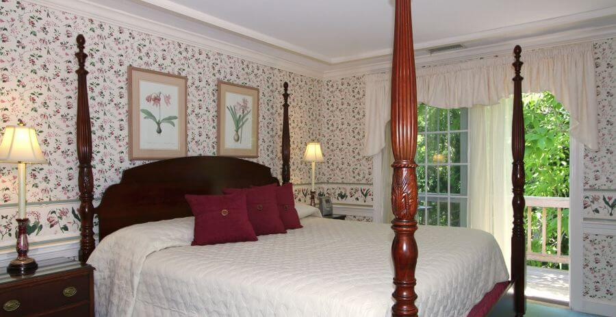 Large four-post bed made up in white in a bedroom with crown moulding and french doors.