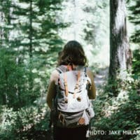 Woman wearing a light backpack who is hiking in a forest