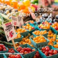 """Baskets of multi-colored cherry tomatoes, stacks of leeks and other fresh veggies with a sign that says """"organic fresh cherry tomatoes."""""""